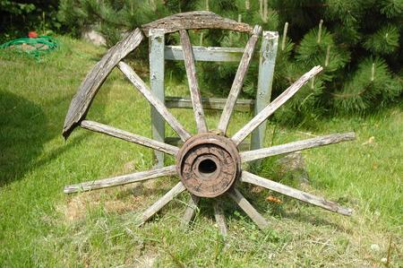 carreta madera: Antiguo devastada rueda de carro de madera en pie en el jard�n