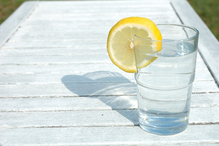lemon water: Glass of water decorated with lemon slice on table Stock Photo