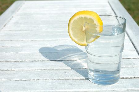 lemon: Vaso de agua decorado con una rodaja de lim�n sobre la mesa Foto de archivo
