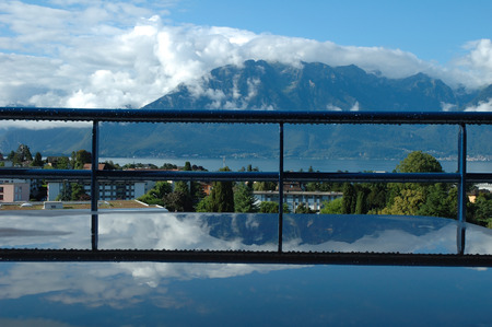 reflected: Mountains at Geneve lake in Switzerland reflected in water on table. Stock Photo