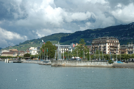 vevey: Vevey, Switzerland - August 16, 2014: Buildings in Vevey at Geneve lake in Switzerland. Unidentified people visible.