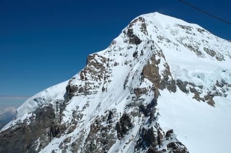jungfraujoch: View from Jungfraujoch pass on Monch peak in Alps in Switzerland Stock Photo