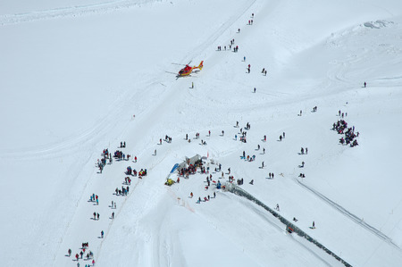 jungfraujoch: Jungfraujoch, Switzerland - August 18, 2014: Unidentified people and rescue helicopter on Jungfraujoch pass in Alps in Switzerland. Editorial