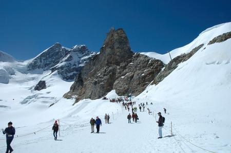 jungfraujoch: Jungfraujoch, Switzerland - August 18, 2014: Unidentified people on trail on Jungfraujoch pass in Alps in Switzerland. Editorial