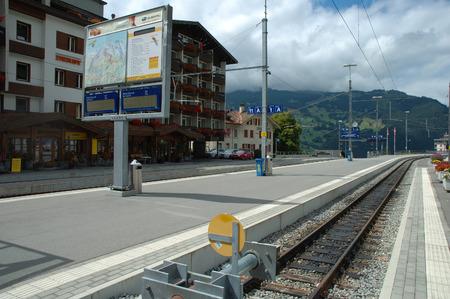 railway tracks: Grindelwald, Switzerland - August 19, 2014: Platform and railway tracks on railway station in Grindelwald in Alps in Switzerland.
