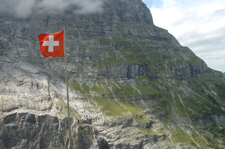 Swiss flag fluttering on wind high in mountains nearby Grindelwald in Alps in Switzerland. photo