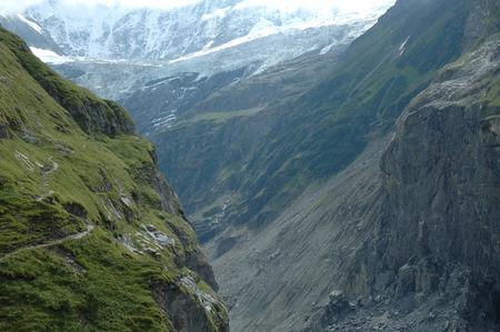 views of the mountains: Deep rocky valley, trail and glacier (Unterer Grindelwaldgletscher) nearby Grindelwald in Alps in Switzerland