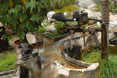 exceptional: Small unique garden fountain made of old metal parts and tree trunk