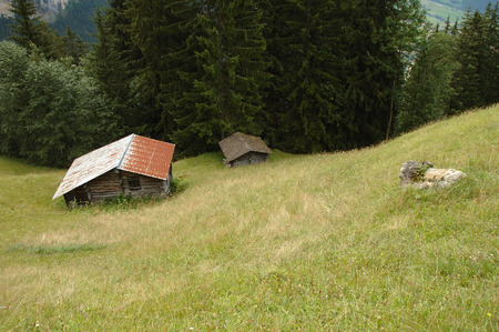 sheds: Two old sheds on meadow in mountains