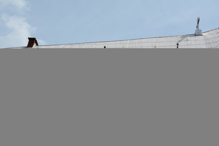 garret: Steep church roof covered with silver corrugated plates. Stock Photo