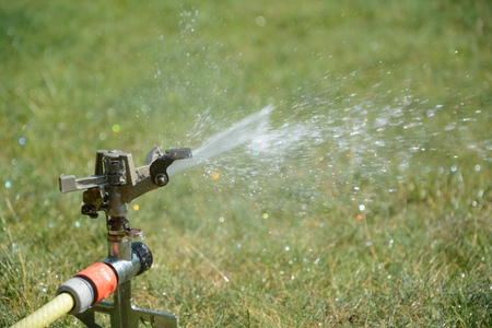 maschine: Sprinkler splashing with water on lawn in garden Stock Photo