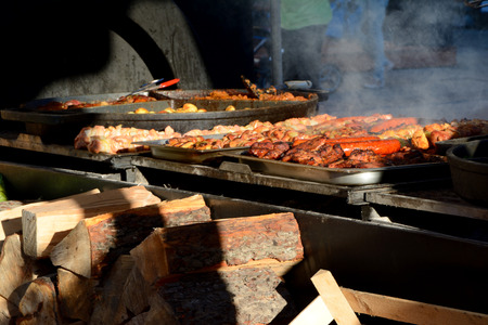 slivers: Slivers of wood and meat cooking on big barbecue
