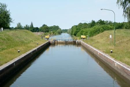 sluice: Canal, sluice gate end electric motors on embankments.