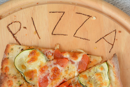scorched: Pizza and pizza word scorched on round wooden plate