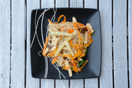 french bean: Dish consisting of chinese rice noodles and cooked vegetables on black plate.