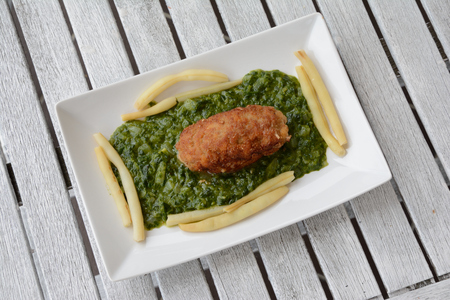 meatloaf: Dish consisting of meatloaf, spinach and bean on white plate.