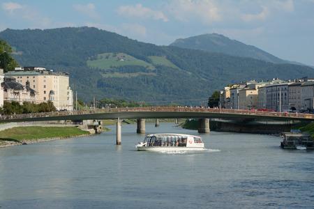 salzach: Salzburg, Austria - September 1, 2015: Passenger boat on Salzach river in Salzburg in Austria. Unidentified people visible.