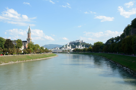 Salzburg, Austria - September 1, 2015: Old city and Hohensalzburg stronghold at Salzach river in Salzburg in Austria. Unidentified people visible.
