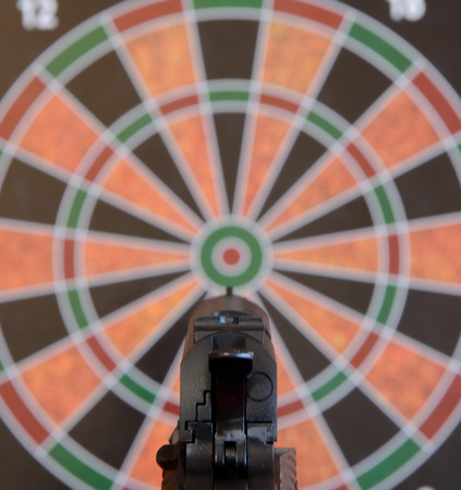 Airsoft gun aiming at target - dartboard