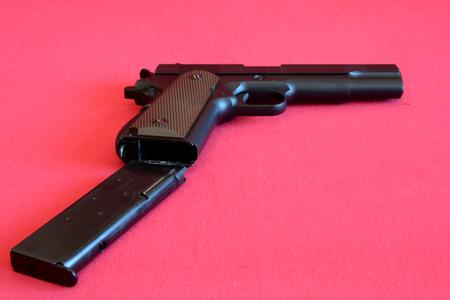 airsoft gun: Airsoft gun and magazine on red fabric.