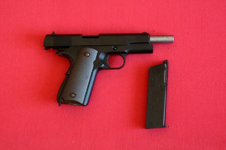airsoft: Airsoft gun and magazine on red fabric.