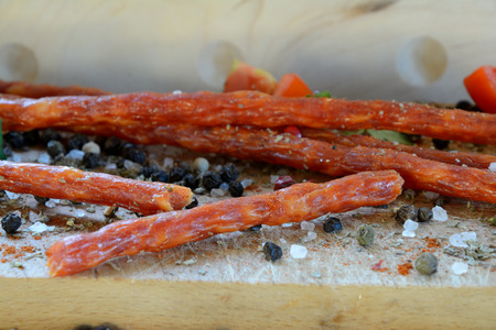 meat dish: Kabanos sausage and spices on wooden chopping board.