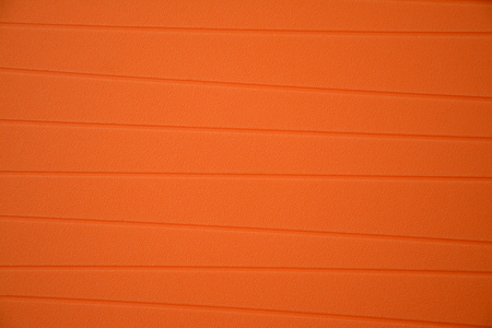 grooves: Orange rubber tablemat with grooves closeup - background Stock Photo
