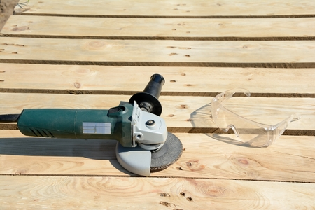 protective glasses: Angle grinder with abrasive disc and protective glasses on planks after work.