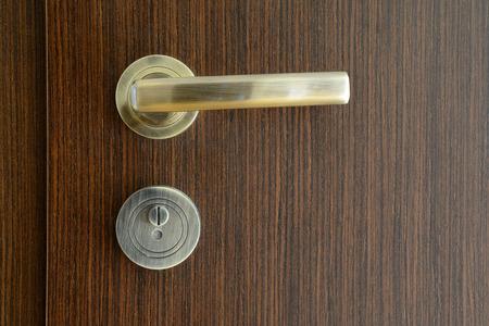 Golden, modern door handle on brown wooden door.
