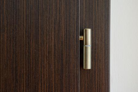 hinge: Golden door hinge on brown wooden door.
