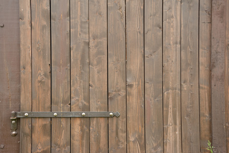 hinge: Hinge and part of brown wooden barn gate