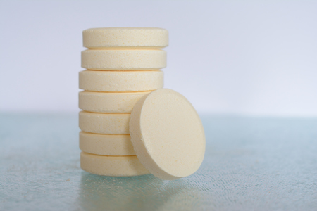 soluble: Pile of soluble tablets on glass table top closeup. Shallow depth of field. Stock Photo