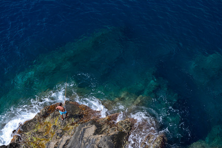 angler: Manarola, Italy - September 4, 2016: Unidetified angler catching fish on rocky shore in Manarola in Liguria, Italy. One of five Cinque Terre cities (unesco world heritage)