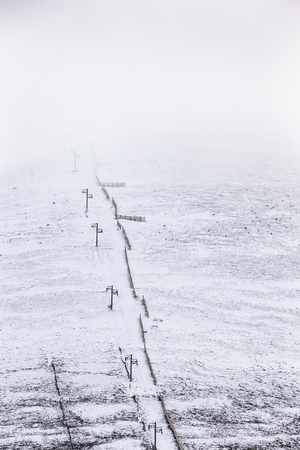 Ski lift and Snow fence on Cairngorm Mountain in Scotland.