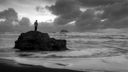Man standing on the rock, at the wild west coast of Auckland, New Zealand