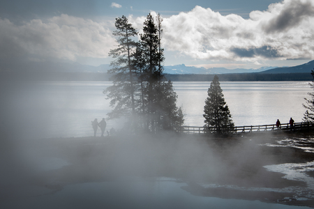 Misty landscape with silhouette people in Yellowstone Nation Park