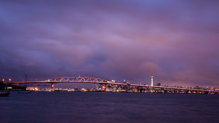 Auckland Harbour Bridge lit up in golden hour for Auckland Anniversary to celebrate the citys birthday