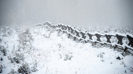 A long fence covered in white snow covered in Grand Teton National park