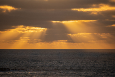 Rays of golden lights at sunset, Muriwai Beach Auckland Stock Photo