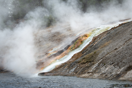 Geyser basin with hot thermal falls running down the colourful rocks at Yellowstone National Park in Wyoming