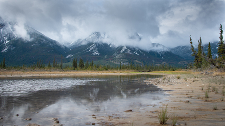 Mountains in clouds reflected in Athabasca river in Jasper Nation Park of Canada