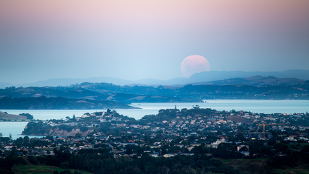 Supermoon rising above Auckland, moonrise and sunset at the same time, view from the top of Mount Eden