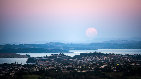 Full moon rising above Auckland, moonrise and sunset at the same time, view from top of Mt Eden