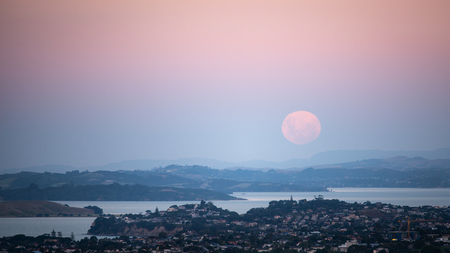 Full moon rising above Auckland, moonrise and sunset at the same time, viewed from Mount Eden