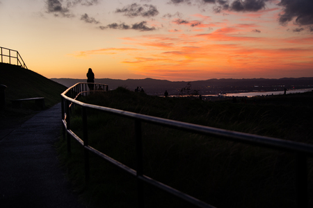 Tourists watching beautiful sunset at Mount Eden, Auckland