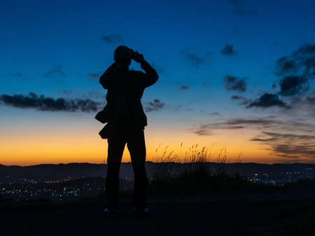 Tourist taking photos of Auckland city at sunset on top of Mount Eden Stock Photo