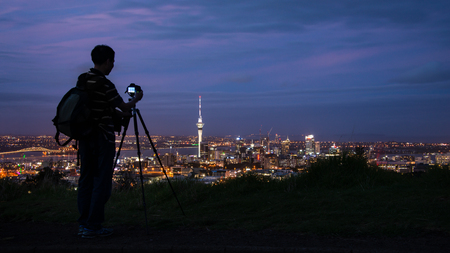 Tourist taking photos of Auckland city at sunset at the top of Mount Eden