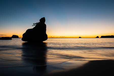 Silhouette rock at first light in Cathedral cove on the Coromandel Peninsula, New Zealand