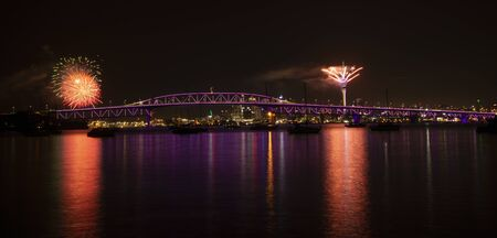 Auckland fireworks for New Year celebration with Harbour Bridge illuminated in purple Stock Photo