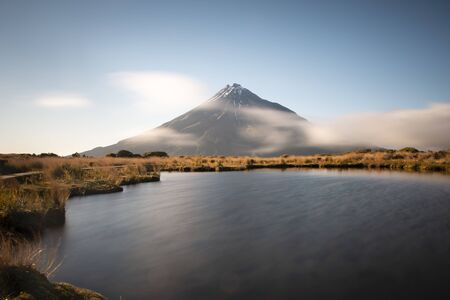 Majestic Mount Taranaki with fast moving clouds Stock Photo